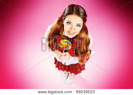 Pretty smiling teen girl in school plaid skirt and white blouse posing with lollipop over pink background. Anime style.