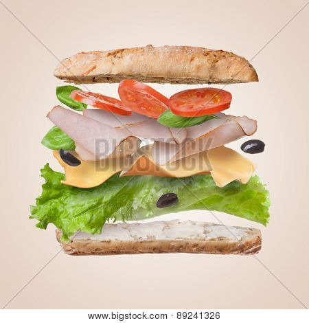 Sandwich with falling ingredients in the air - slices of fresh tomatoes, ham, cheese and lettuce