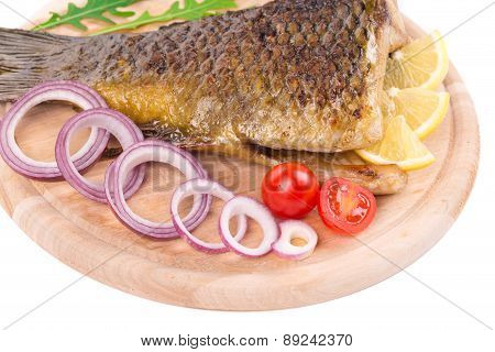 Grilled carp with lemon and tomatoes.