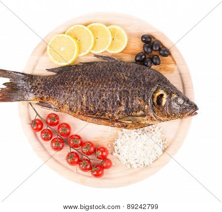 Grilled carp fish with lemon and tomatoes.