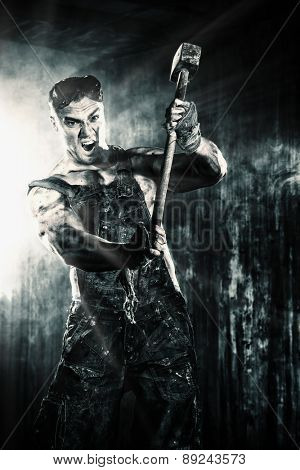 Strong aggressive coal miner with a hammer over dark grunge background. Mining industry. Art concept. Toned photo, old style.