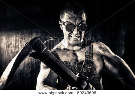 Muscular dirty coal miner with a pickaxe over dark grunge background. Mining industry. Art concept. Toned photo, old style.