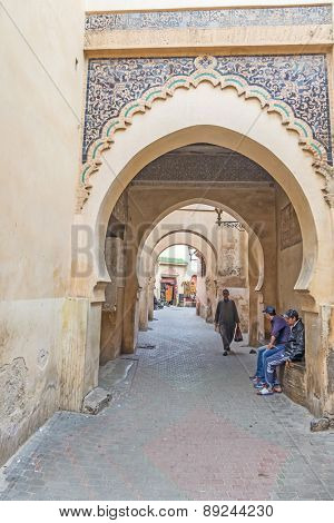 MARRAKESH, MOROCCO, APRIL 4, 2015: Men sit near the entrance to The Ben Youssef Madrasa