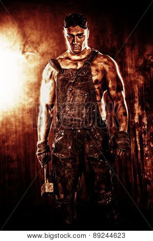 Handsome muscular coal miner with a hammer over dark grunge background. Mining industry. Art concept.