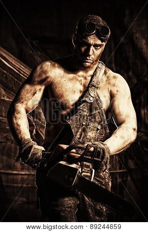 Handsome muscular man with a chainsaw over dark grunge background. Sepia.