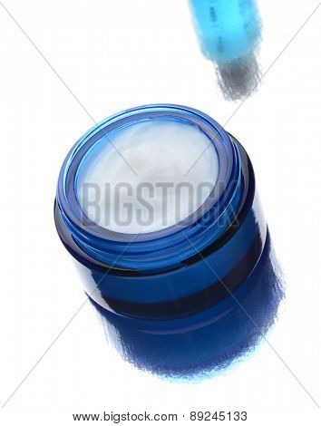 Closeup of a blue jar filled with facial cream with reflection. A second products reflection is in the background.