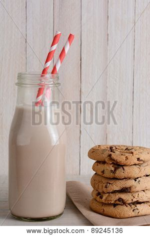 Closeup of a bottle of chocolate milk and a stack of chocolate chip cookies in a rustic kitchen set.