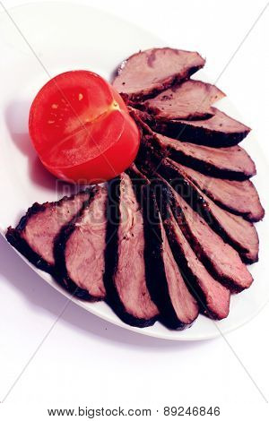 meat table : rare medium roast beef fillet with tomatoes on white plate isolated over white background