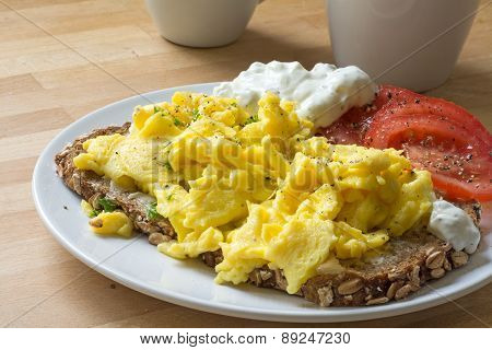 Scrambled Eggs On Rustic Bread With Tomatoes And Curd Cheese Cream