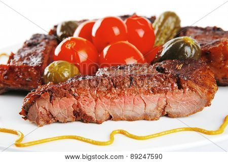roast beef meat steak with cherry tomatoes and salted cucumbers on white plate isolated over white background