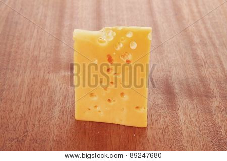 bit of aged french gold emmental or cheddar cheese on wooden table