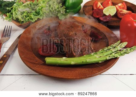 grilled roast red beef meat served on wooden dishes with peppers cutlery salad and vegetables on white wooden table