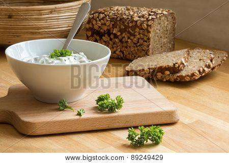Curd Cheese Dip With Herbs In A Bowl And Rustic Bread In The Background