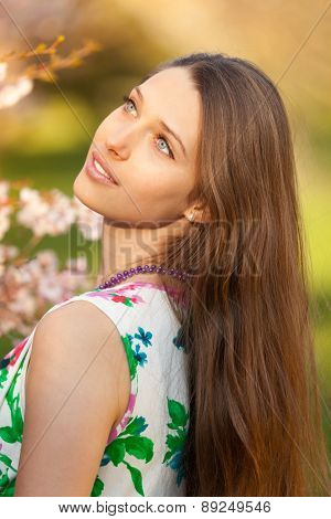 Beautiful young brunette woman in blooming orchard
