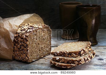 Wholegrain Bread With Seeds On Weathered Wood, Dark Background