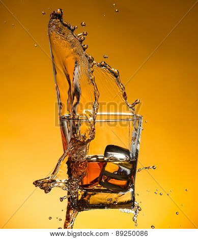 Whiskey with ice with liquid splash, freeze motion.