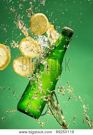 Green beer bottle with splashing liquid, freeze motion.