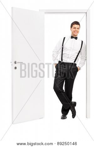 Full length portrait of a handsome young man in elegant clothes posing by an opened door isolated on white background