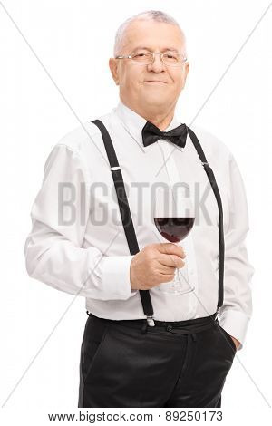 Vertical shot of an elegant senior gentleman holding a glass of red wine and looking at the camera isolated on white background