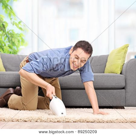Young man vacuuming a carpet with a handheld vacuum cleaner and smiling at home shot with tilt and shift lens
