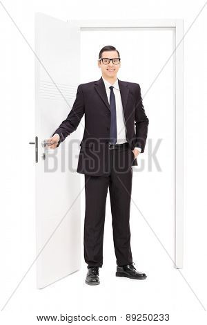 Full length portrait of a young businessman in a black suit posing in front of an opened door isolated on white background