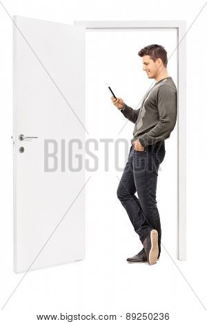 Full length portrait of a young man surfing the net on his cell phone and leaning on the frame of an opened door isolated on white background