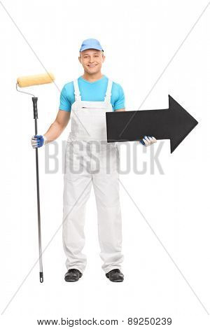 Full length portrait of a young male decorator in a white uniform holding a paint roller and a big black arrow pointing right isolated on white background
