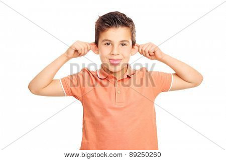 Silly boy in an orange shirt making a grimace and sticking his tongue out isolated on white background