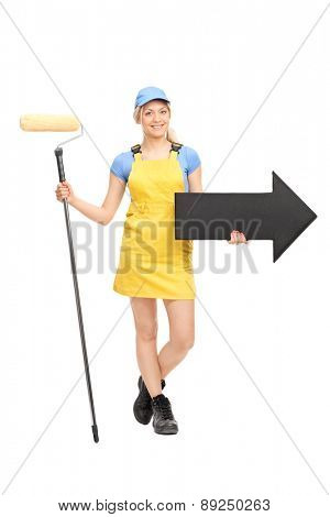 Full length portrait of a female painter in a yellow uniform holding a paint roller and a big black arrow pointing right isolated on white background