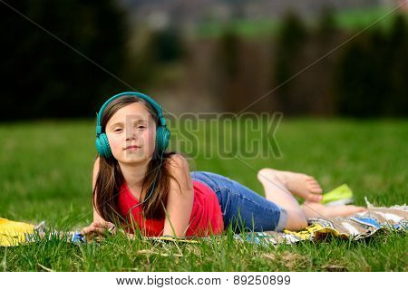 A Pretty Young Girl Listening To Music In Nature