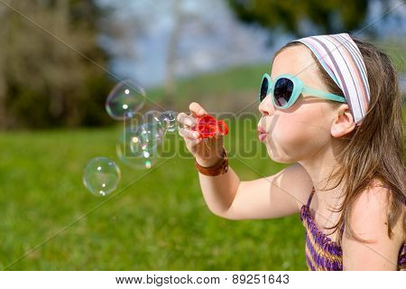A Little Girl Making Soap Bubbles