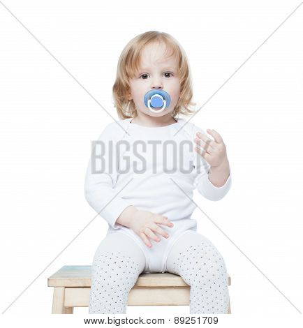 Baby little girl with long hair and a pacifier pacifier sitting on a stool, isolation