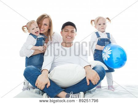Family, father sitting on a cushion behind it little girls twins and a beautiful wife, isolation