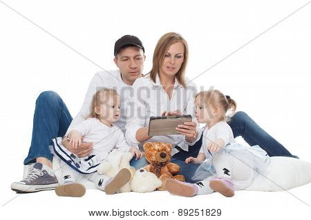 Family, mom and dad sit on a cushion near the little twin girls sit and look at Tablet Computer, iso
