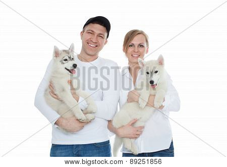 Beautiful family, a man and woman holding hands on the husky puppies, isolation