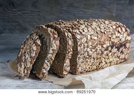 Dark Bread Loaf With Whole Grain And Seeds On An Old Wooden Board