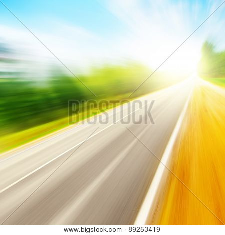 Country asphalt road in motion blur and sunlight.