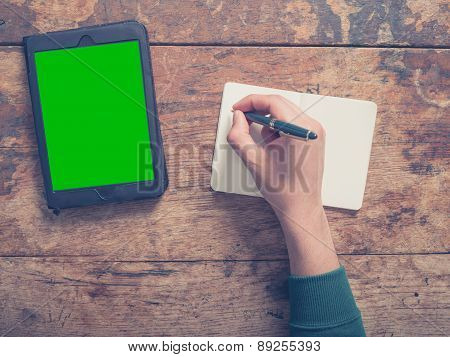 Male Hand Writing In Notepad And Using Tablet