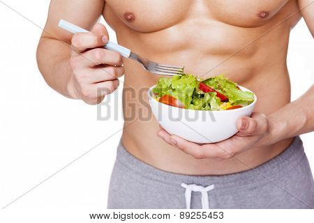 Strong fitness man holding a bowl of salad, isolated on white background