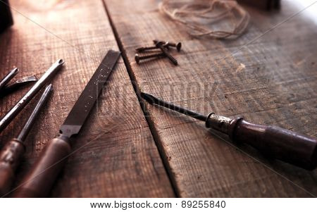 Old and well used tools on a aged wooden work bench, with incoming light. Old screw driver, file on desk. Focus on screw driver tip. Intentionally shot with shallow depth of focus and vintage tone.