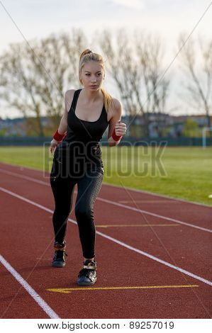 Young Woman Running At A Track And Field Stadium