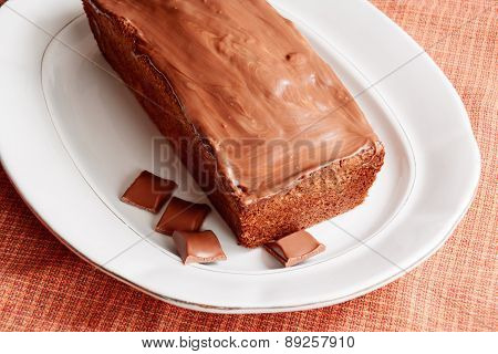 Cake With Glaze Of Chocolate In The White Dish