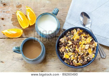 Breakfast Granola With Milk, Coffee And Sliced Oranges On A Weathered Wood From Above