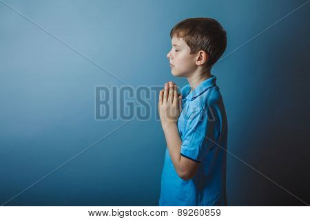 boy teenager European appearance in a blue shirt brown praying l