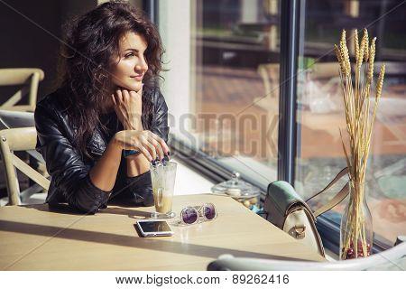 Brunette Beautiful Stylish Caucasian Woman In Casual Outfit On A Walk On European City Street Sittin