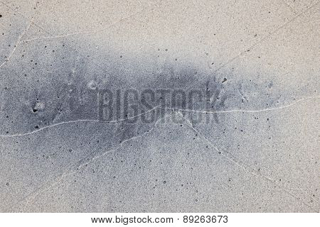 Grey and beige abstract background of wet sand texture formed by waves on beach