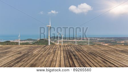 Wind turbines on landscape along empty road against sky.