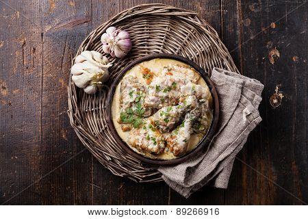 Roasted Chicken With Creamy Garlic Sauce In Clay Pan Ketsi On Dark Wooden Background