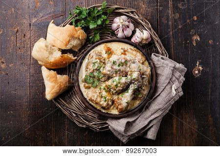 Roasted Chicken With Creamy Garlic Sauce In Clay Pan Ketsi On Dark Wooden Background
