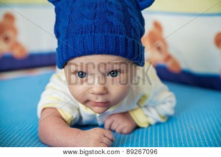 little child lying on a children's rug in the blue cap